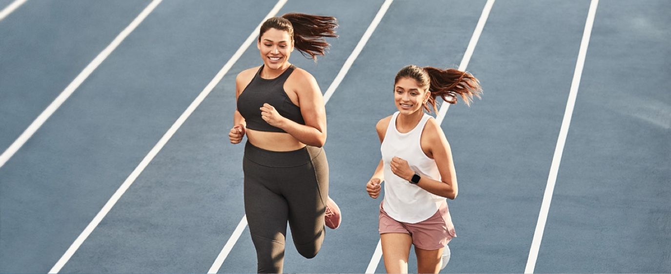 two young women jogging on a track